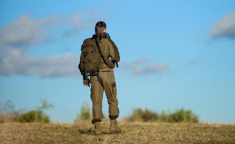 Il cacciatore dell'uomo porta il fondo del cielo blu del fucile L'esperienza e la pratica presta la caccia di successo Hobby di c fotografie stock libere da diritti