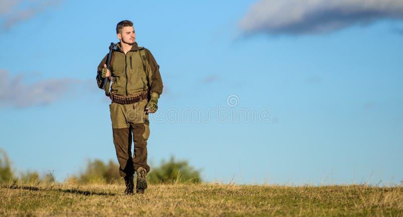 Il cacciatore dell'uomo porta il fondo del cielo blu del fucile L'esperienza e la pratica presta la caccia di successo Pistola o  fotografia stock libera da diritti