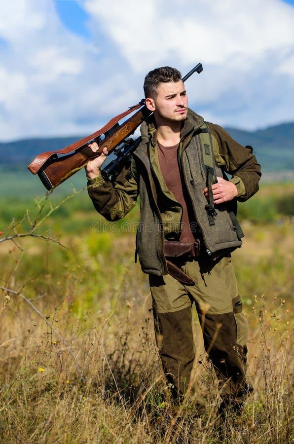 Il cacciatore dell'uomo porta il fondo della natura del fucile L'esperienza e la pratica presta la caccia di successo Ambiente de immagini stock