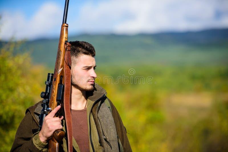 Il cacciatore dell'uomo porta il fondo della natura del fucile L'esperienza e la pratica presta la caccia di successo Ambiente de fotografia stock