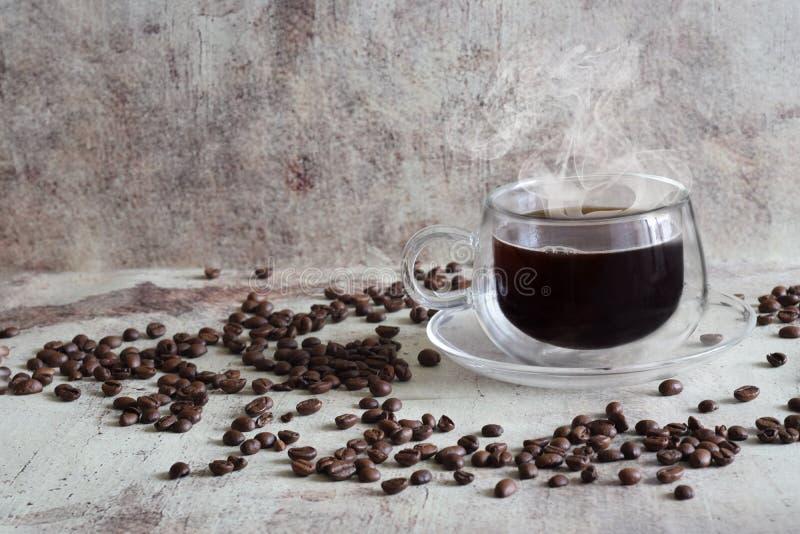 Il caffè caldo in una bella tazza trasparente, chicchi di caffè ha sparso caotico su un fondo grigio d'annata fotografia stock