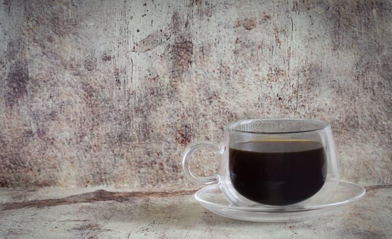 Il caffè caldo in una bella tazza trasparente con un piattino di vetro ha fotografato il primo piano su un fondo grigio d'annata fotografia stock
