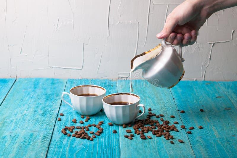 Il caffè con latte, versa il latte dal lattaio, backgr di legno blu fotografie stock