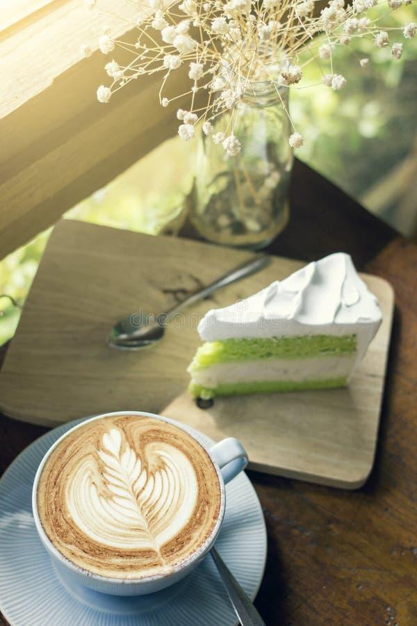Il caffè del cappuccino con arte del latte ed il dolce affettano i dessert fotografie stock libere da diritti
