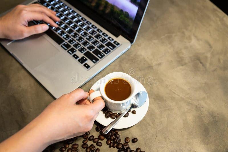Il caffè del caffè espresso in una tazza di caffè caldo e dei chicchi di caffè, mani della donna sta funzionando, facendo uso di  fotografie stock