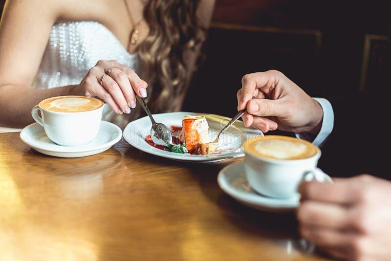 Il caffè dello sposo e della sposa e dolce beventi di cibo in un caffè alla tavola di legno fotografia stock