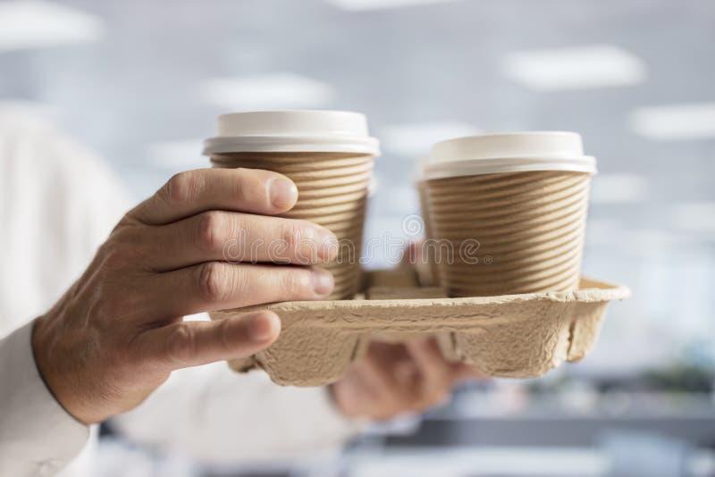 Il caffè di trasporto dell'uomo d'affari elimina le tazze eliminabili in ufficio f immagine stock