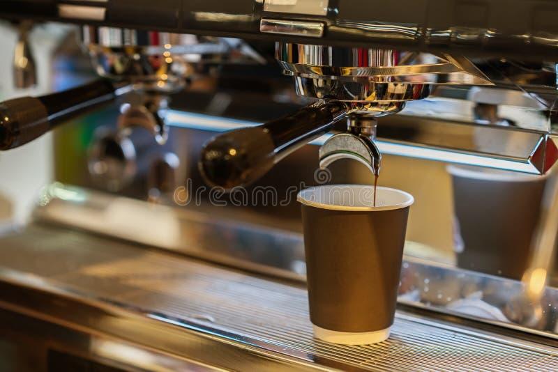 Il caffè espresso fresco del primo piano versa dentro la tazza di carta, macchina di caffè espresso italiana Cultura del caffè e  immagine stock libera da diritti