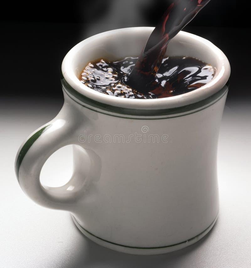 Il caffè versa dentro il vapore caldo della tazza fotografia stock