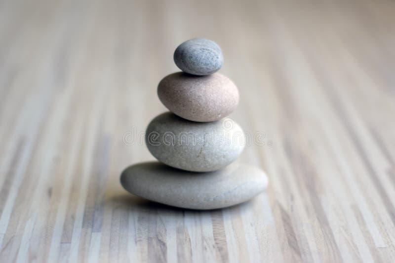 Il cairn di pietra sul fondo a strisce di bianco grigio, quattro pietre si eleva, pietre semplici di equilibrio, armonia di sempl fotografie stock