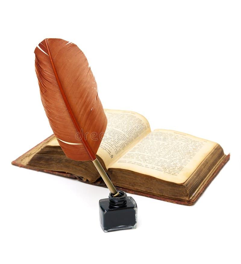 Il calamaio, penna ed apre il vecchio libro su fondo bianco fotografie stock