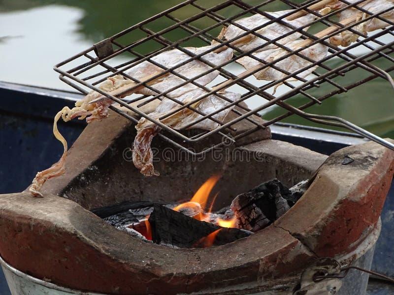 Il calamaro secco è essere grigliatoe pronto usando il carbone immagini stock