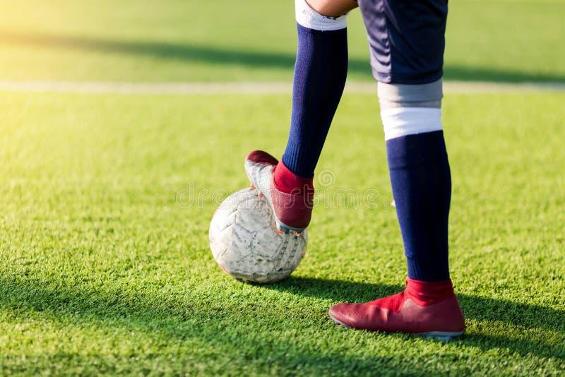 Il calciatore salta e batte i piedi per la trappola ed il calcio di controllo immagini stock