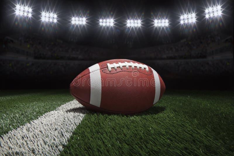 Il calcio di stile dell'istituto universitario sul campo con la banda sotto lo stadio si accende immagini stock libere da diritti
