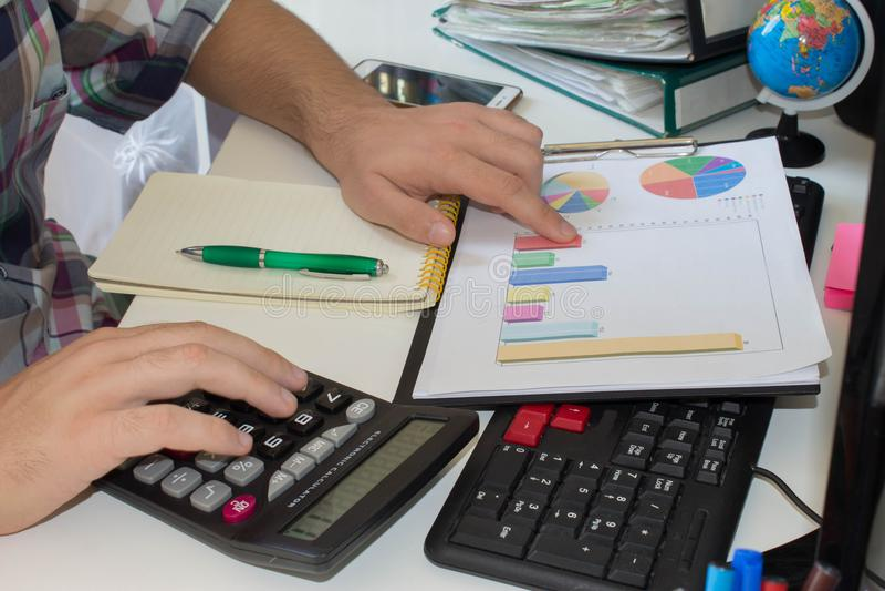 Il calcolatore con l'uomo del ` s della mano calcola la finanza sull'ufficio dello scrittorio a casa immagine stock