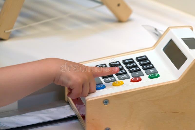 Il calcolatore dei bambini Il bambino impara contare su una calcolatrice elettronica immagine stock