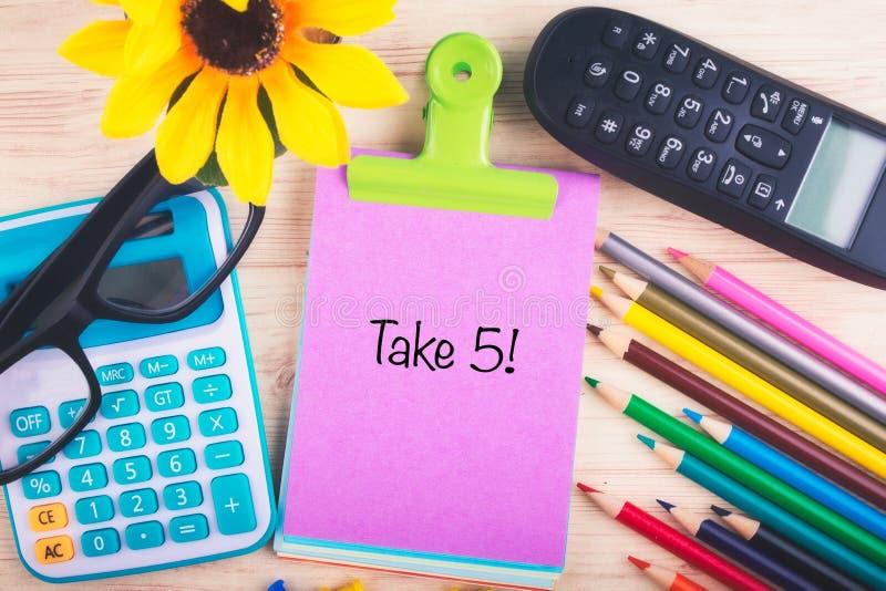 Il calcolatore, matite, puntine da disegno e PRENDE la parola 5 scritta sul blocco note fotografia stock libera da diritti