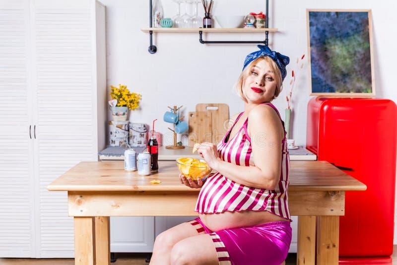Il cambiamento delle preferenze del gusto durante la gravidanza, il modello incinto mangia felice le patatine fritte fotografia stock
