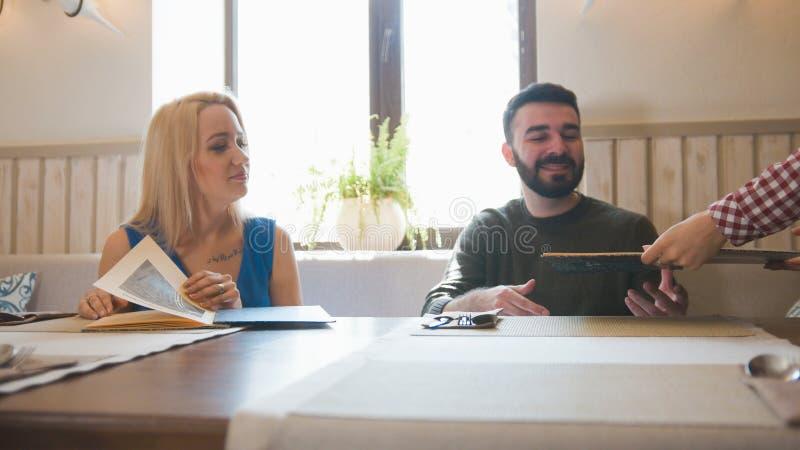 Il cameriere in caffè mostra il menu per le giovani coppie immagini stock