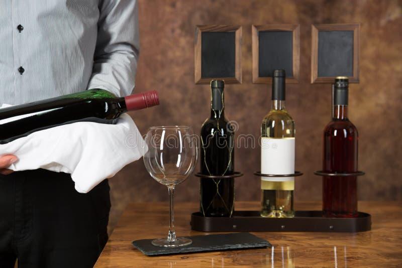Il cameriere comincia versare il vino rosso in un vetro immagini stock libere da diritti