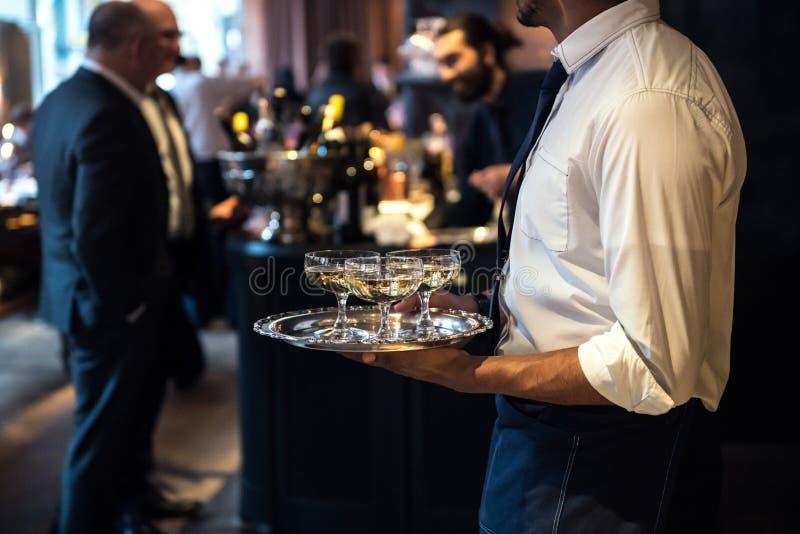Il cameriere dal vino di trasporto del champagne di servizio di approvvigionamento beve sull'evento immagini stock libere da diritti