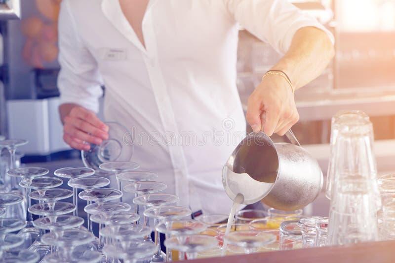 Il cameriere nel succo di versamento della barra dal lanciatore del ferro, dof basso fotografie stock libere da diritti