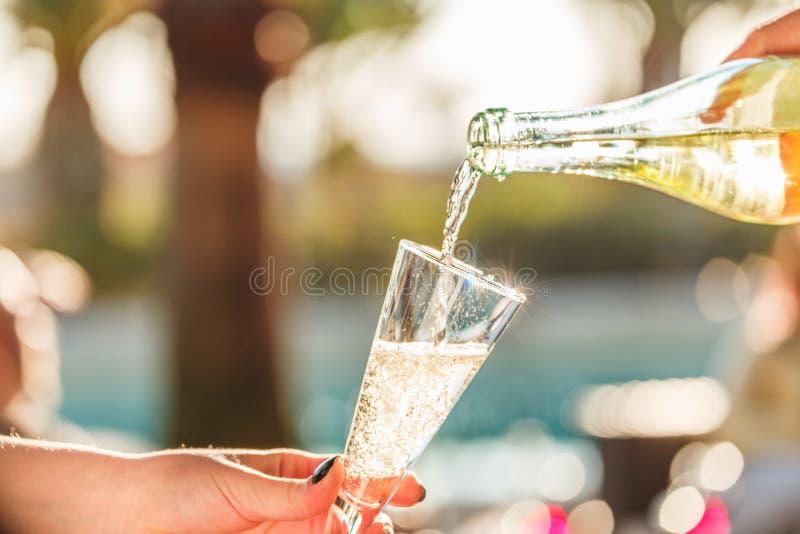 Il cameriere pourring il vino spumante in un vetro della donna al partito all'aperto Concetto di celebrazione immagini stock