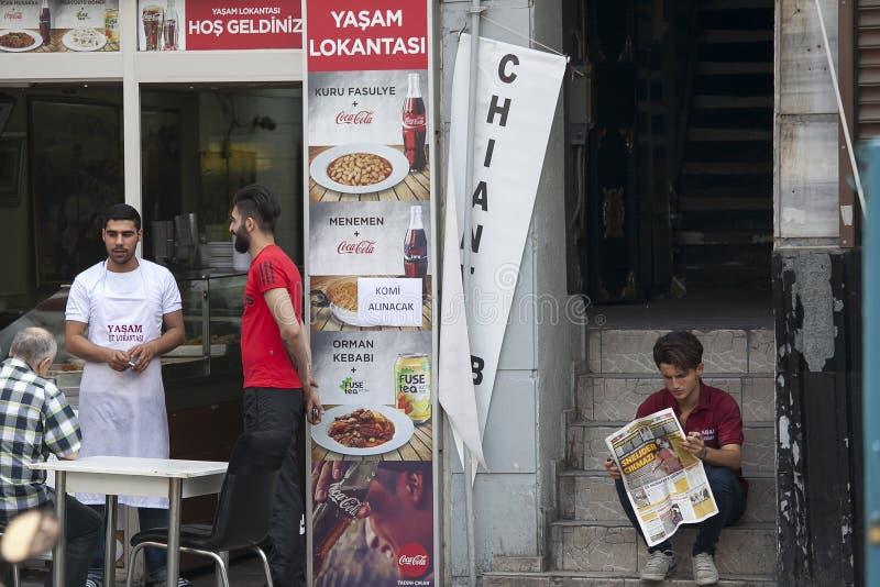 Il cameriere serve gli ospiti in un caffè della via Un giovane che legge un giornale, sedentesi sui punti immagine stock libera da diritti