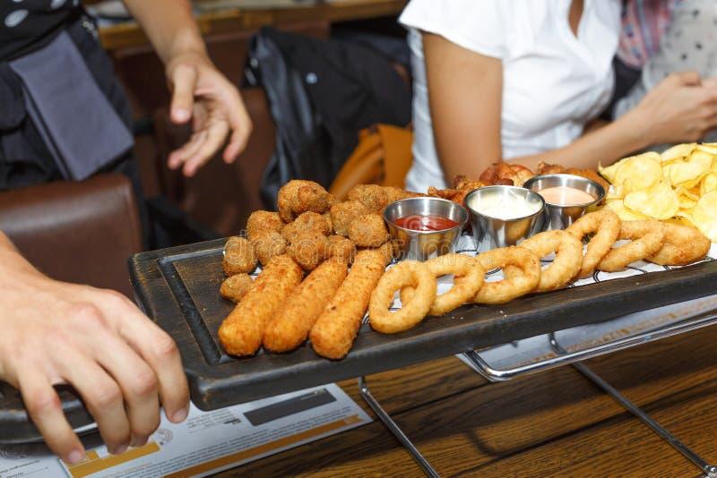 Il cameriere serve nei vari spuntini, birra e salse della barra Pepite di pollo, chip, anelli di cipolla, ali di pollo fritto su  fotografie stock