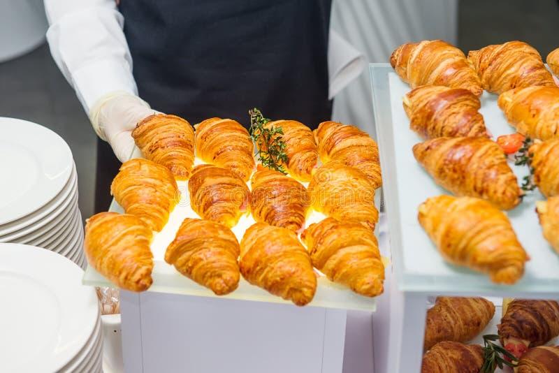 Il cameriere servering la tavola di buffet di approvvigionamento con alimento e fa un spuntino per gli ospiti dell'evento Pranzar immagini stock