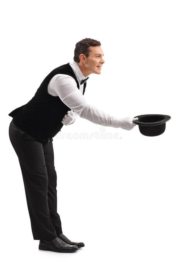 Il cameriere si inchina e decollando il suo cappello immagini stock libere da diritti