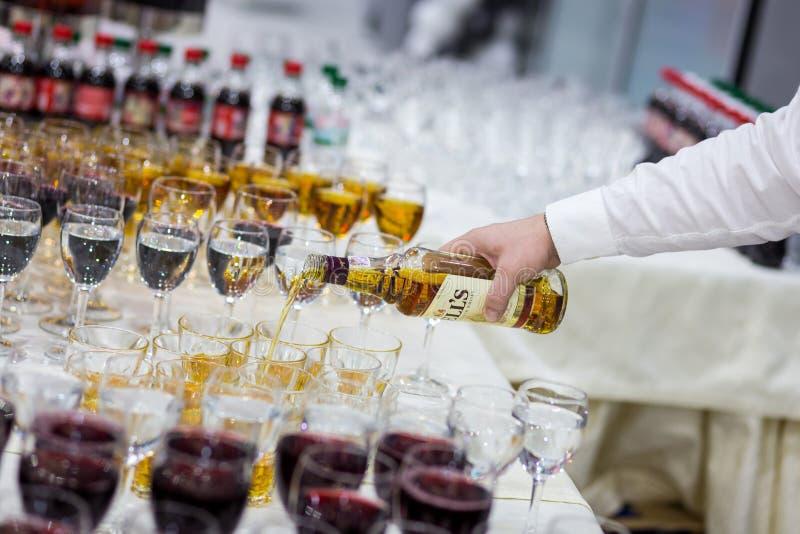 Il cameriere versa il whiskey in un vetro vetri sul tabl bianco immagini stock libere da diritti
