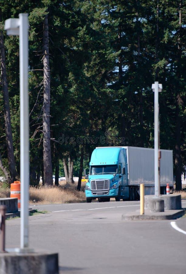 Il camion blu dei semi del grande impianto di perforazione con il rimorchio dei semi accende l'uscita per riposare la a immagini stock