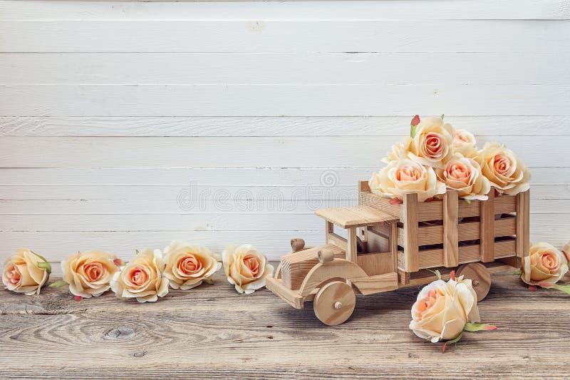 Il camion di legno del giocattolo con le rose della pesca fiorisce nella parte posteriore su un bianco fotografia stock libera da diritti