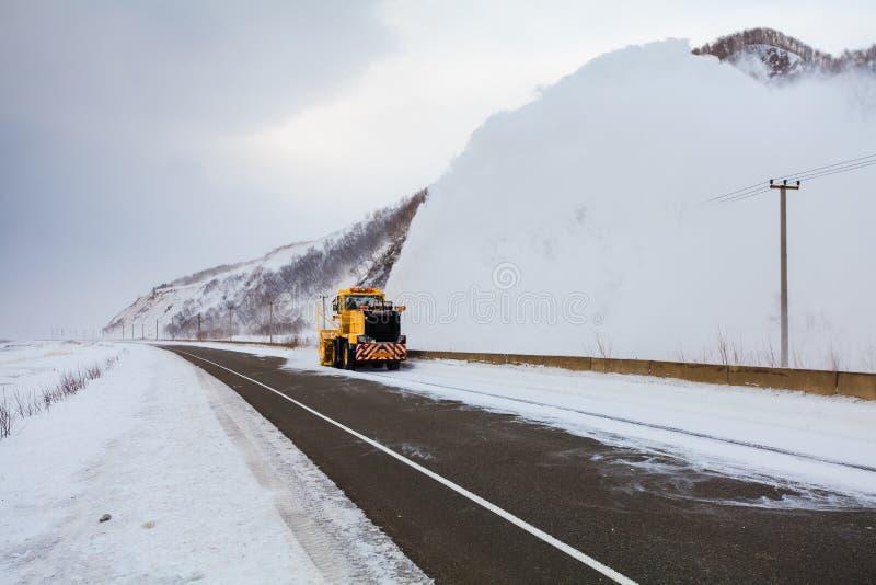 Il camion di rimozione di neve del camion dello spazzaneve sta rimuovendo la neve dalla strada principale immagine stock libera da diritti