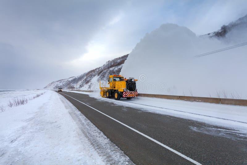 Il camion di rimozione di neve del camion dello spazzaneve sta rimuovendo la neve dalla strada principale durante il giorno di in immagine stock libera da diritti