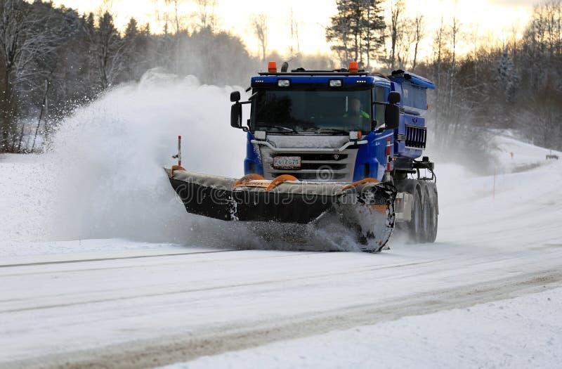 Il camion di Scania con lo spazzaneve rimuove la strada principale fotografie stock