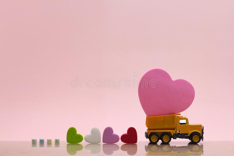 Il camion giallo del giocattolo continua il cuore rosa su fondo rosa immagini stock