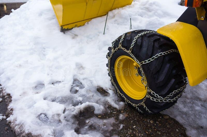 Il camion giallo dello spazzaneve ha rimosso la strada innevata nell'inverno da immagine stock
