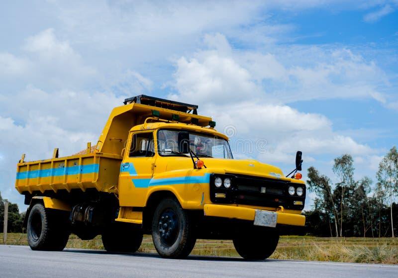 Il camion giallo sulla strada con il bei cielo ed azienda agricola fotografia stock