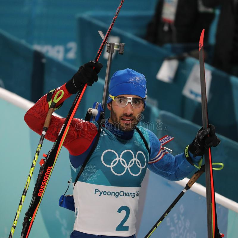 Il campione olimpico Martin Fourcade della Francia celebra la vittoria nell'inizio di massa del ` s 15km degli uomini di biathlon fotografia stock