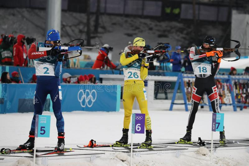 Il campione olimpico Martin Fourcade della Francia fa concorrenza nell'inizio di massa del ` s 15km degli uomini di biathlon alle fotografia stock