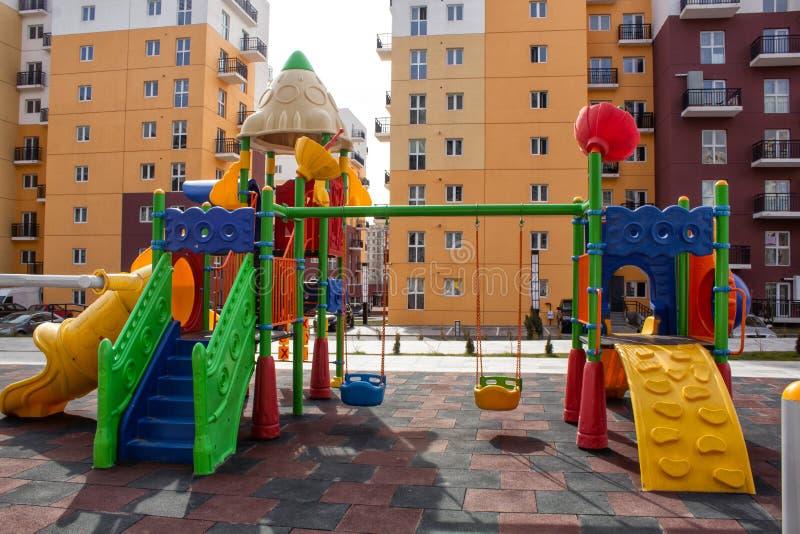 Il campo da gioco per bambini con gli scorrevoli e le oscillazioni nel cortile degli edifici residenziali immagini stock
