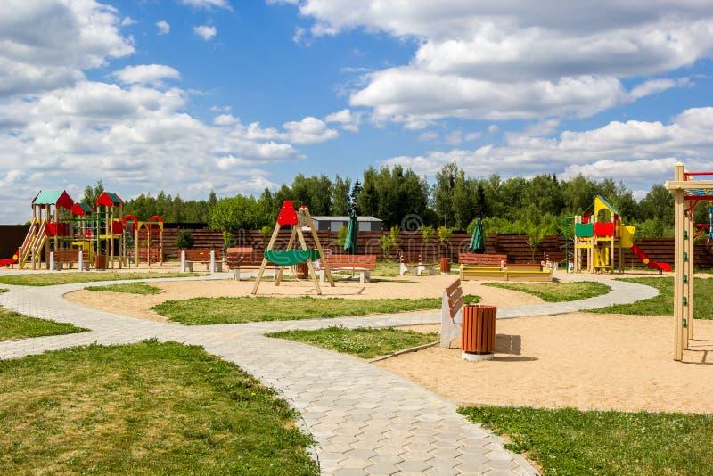 Il campo da gioco per bambini con le oscillazioni e la campagna degli scorrevoli fotografia stock libera da diritti