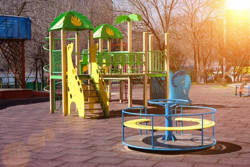 Il campo da gioco per bambini nel cortile di una costruzione a più piani di oscillazioni e di scorrevoli colorati Multi sono inst fotografia stock