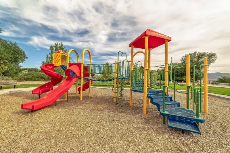 Il campo da gioco per bambini su un parco di rilassamento con la vista degli alberi e della montagna distante immagini stock