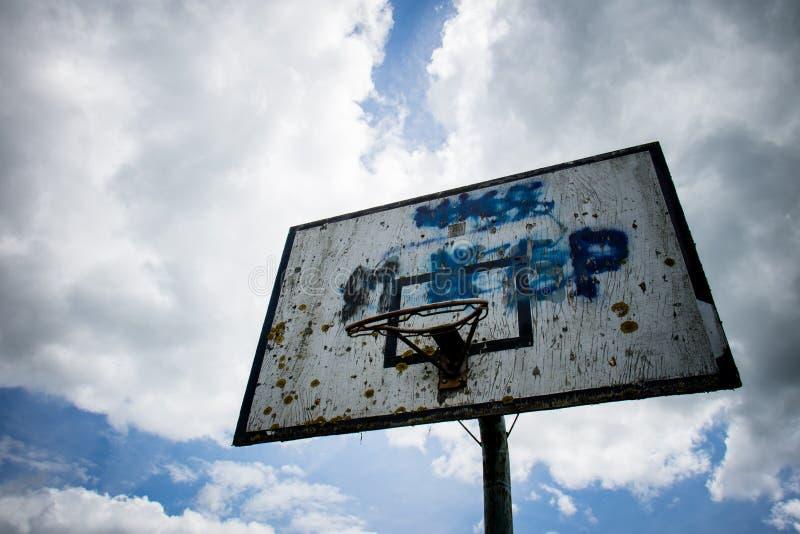 Il campo da pallacanestro anziano, canestro, ha strappato il reticolato contro il cielo immagine stock