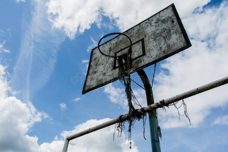 Il campo da pallacanestro anziano, canestro, ha strappato il reticolato contro il cielo fotografie stock