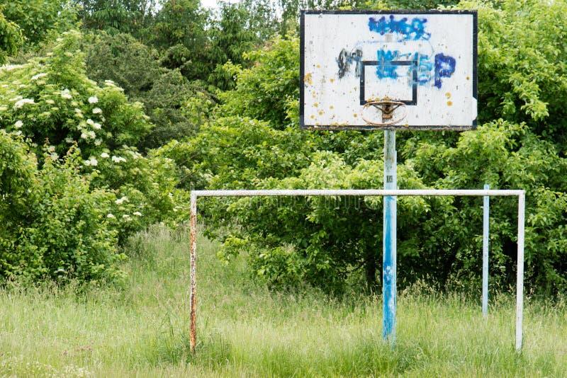 Il campo da pallacanestro anziano, canestro, ha strappato il reticolato contro il cielo fotografia stock