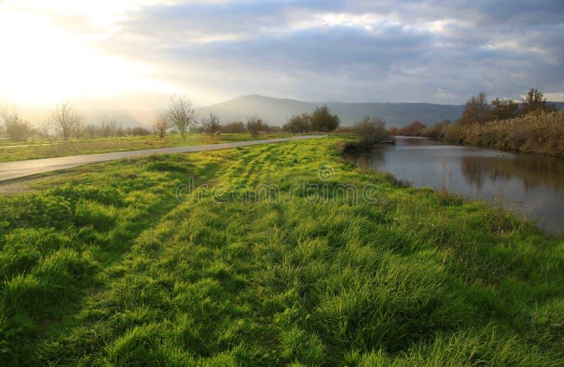 Il campo ed il fiume verdi si sono accesi dalla forte luce di Sun fotografie stock libere da diritti